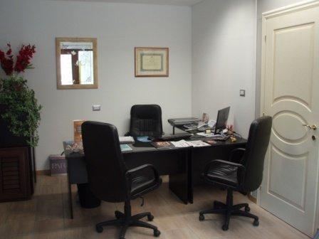 vista di un ufficio cabina con tavolo, sedie, pavimento in legno e porta interna in legno