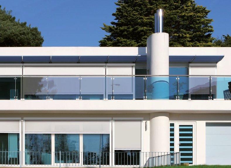 vista frontale di un impianto edificio con parapetto in vetro e tende da sole