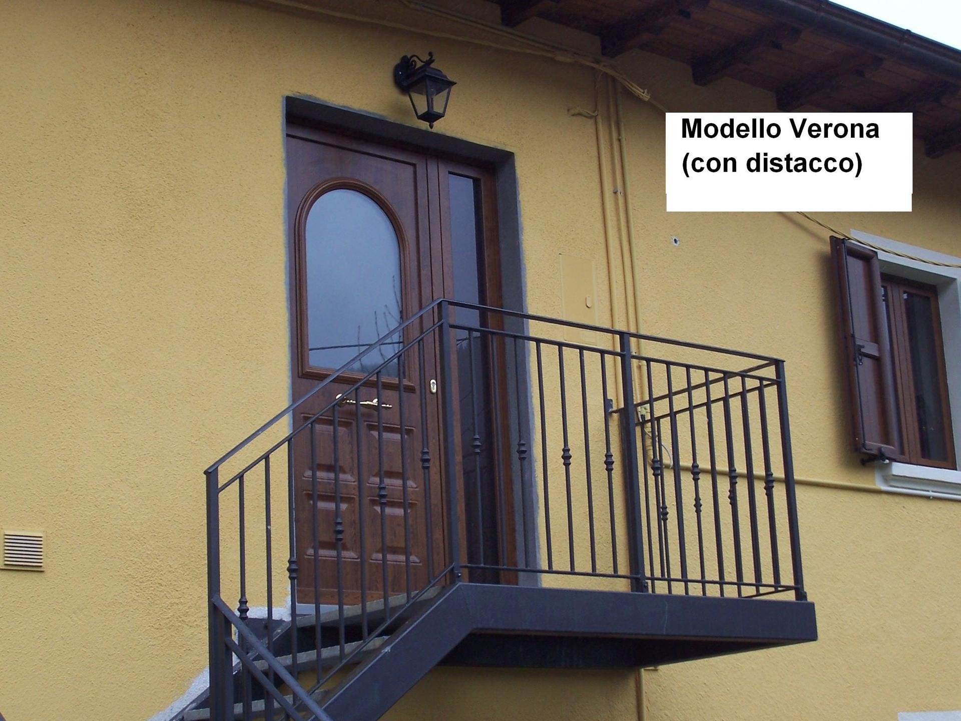 vista di una casa gialla con porta in legno e vetro e ringhiera in scala  Modello Verona