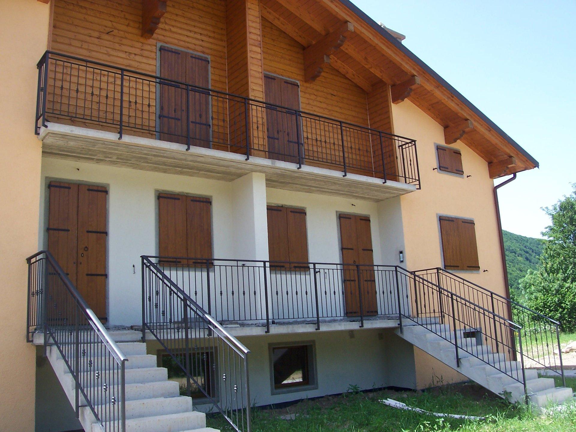 vista frontale di una casa con ringhiera in balcone e scala