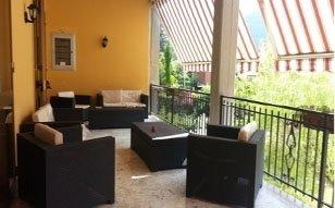 vista laterale del balcone con divani e tavolo