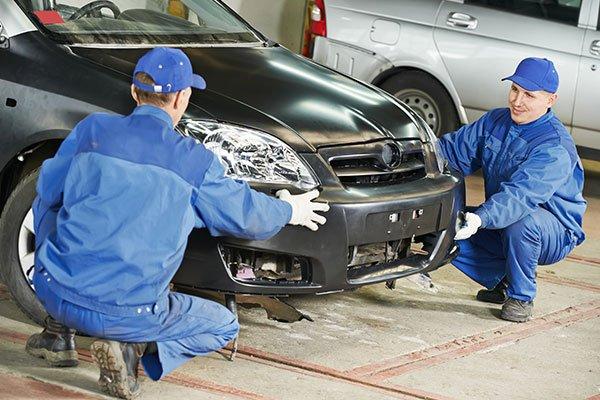 Two repairman mechanics matching an automobile body bumper in Norwich