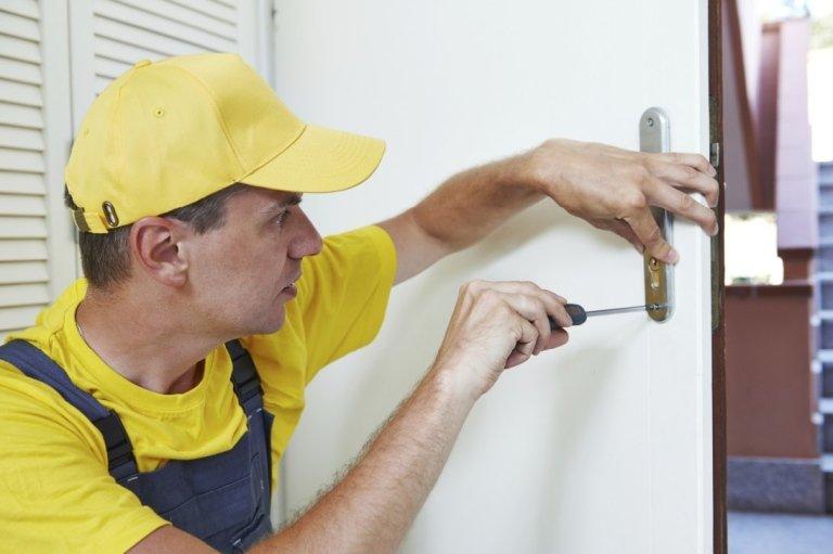 tecnico che ripara con un cacciavite la serratura di una porta