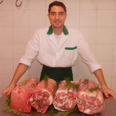 macellaio in posa dietro a preparazione di carne