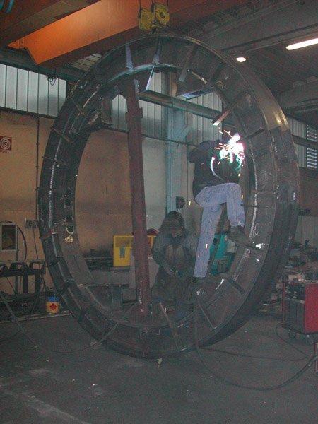 operai lavorano su un grande cerchio in ferro