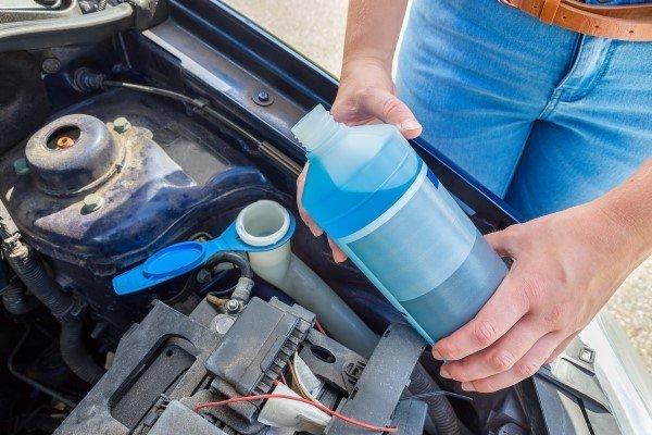 Woman filling car reservoir with blue fluid in bottle