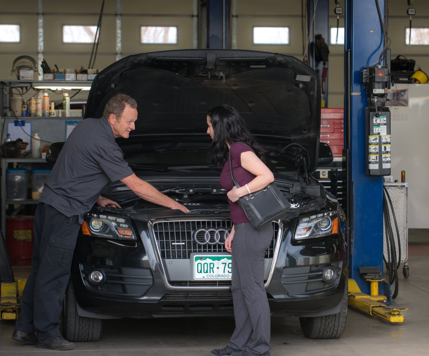 Mechanic repairing a woman's car