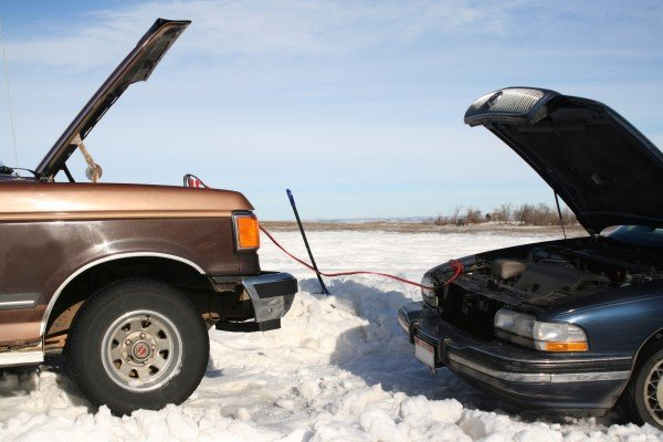 One car helping another to jump start in winter