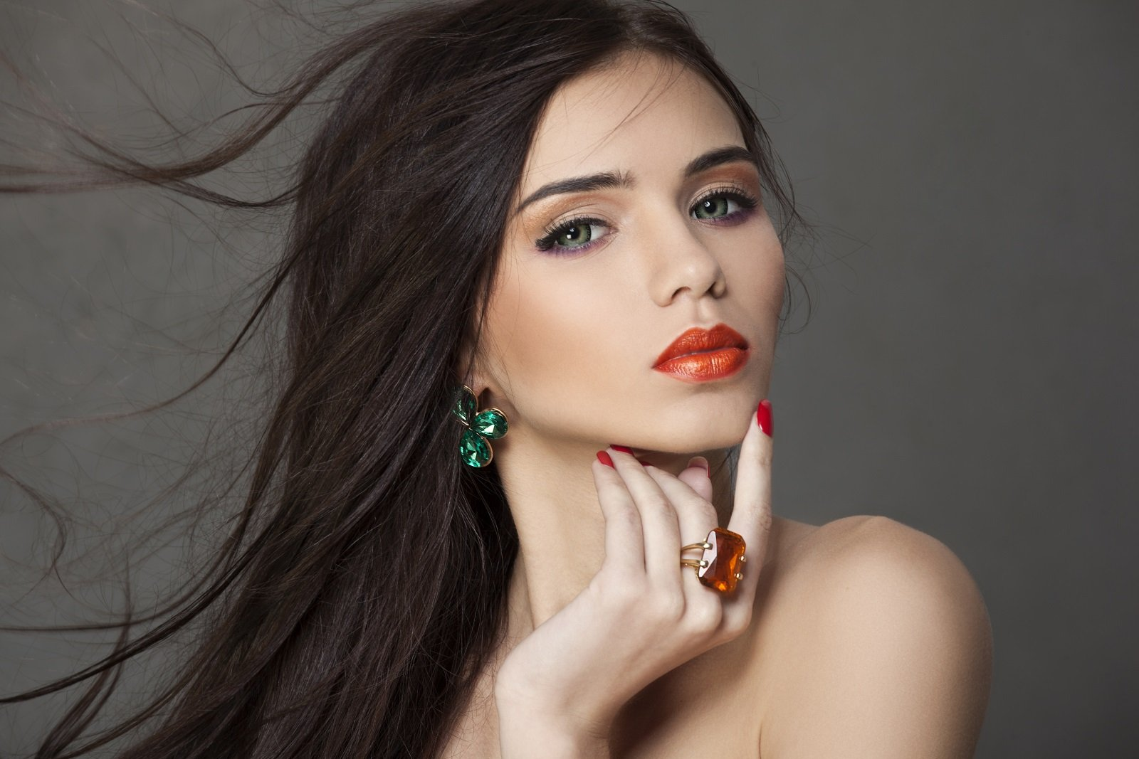 una donna con un orecchino di color verde e un anello con una pietra arancione