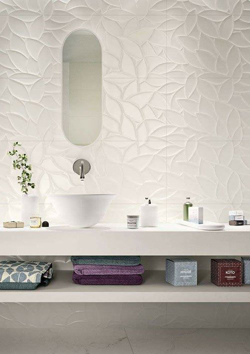 Bagno bianco, lavandino di design e parete di piastrelle con disegno di foglie