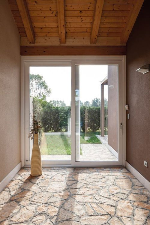 Suolo di pietra e tetto di legno, porta scorrevole in PVC bianco