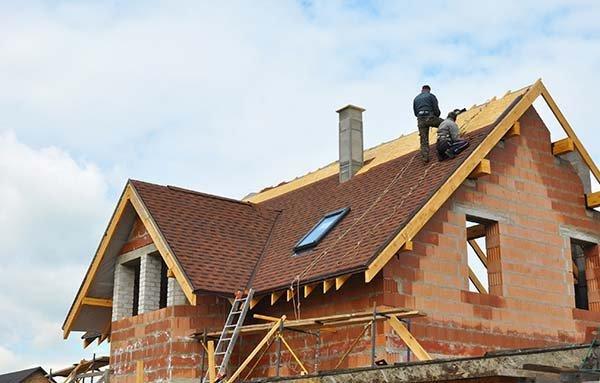 operai sistemano alcune travi su un tetto