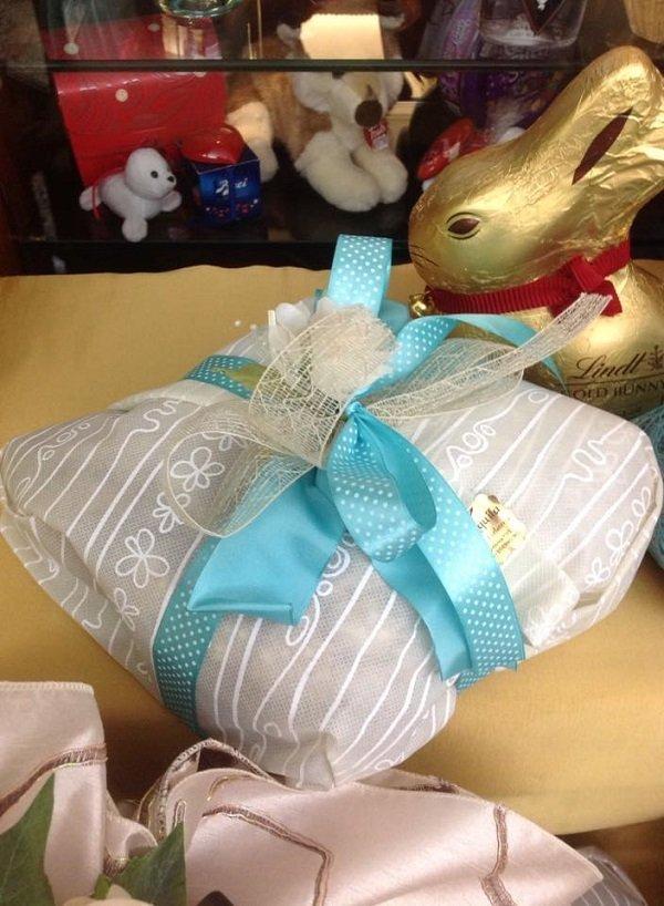 un pacco regalo con un nastro azzurro e accanto un cioccolato a forma di coniglio