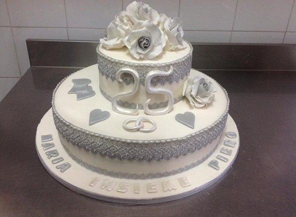 una torta d' anniversario a due piani con delle rose