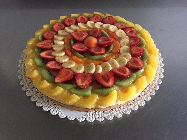 una crostata con delle fette di fragole, kiwi e ananas