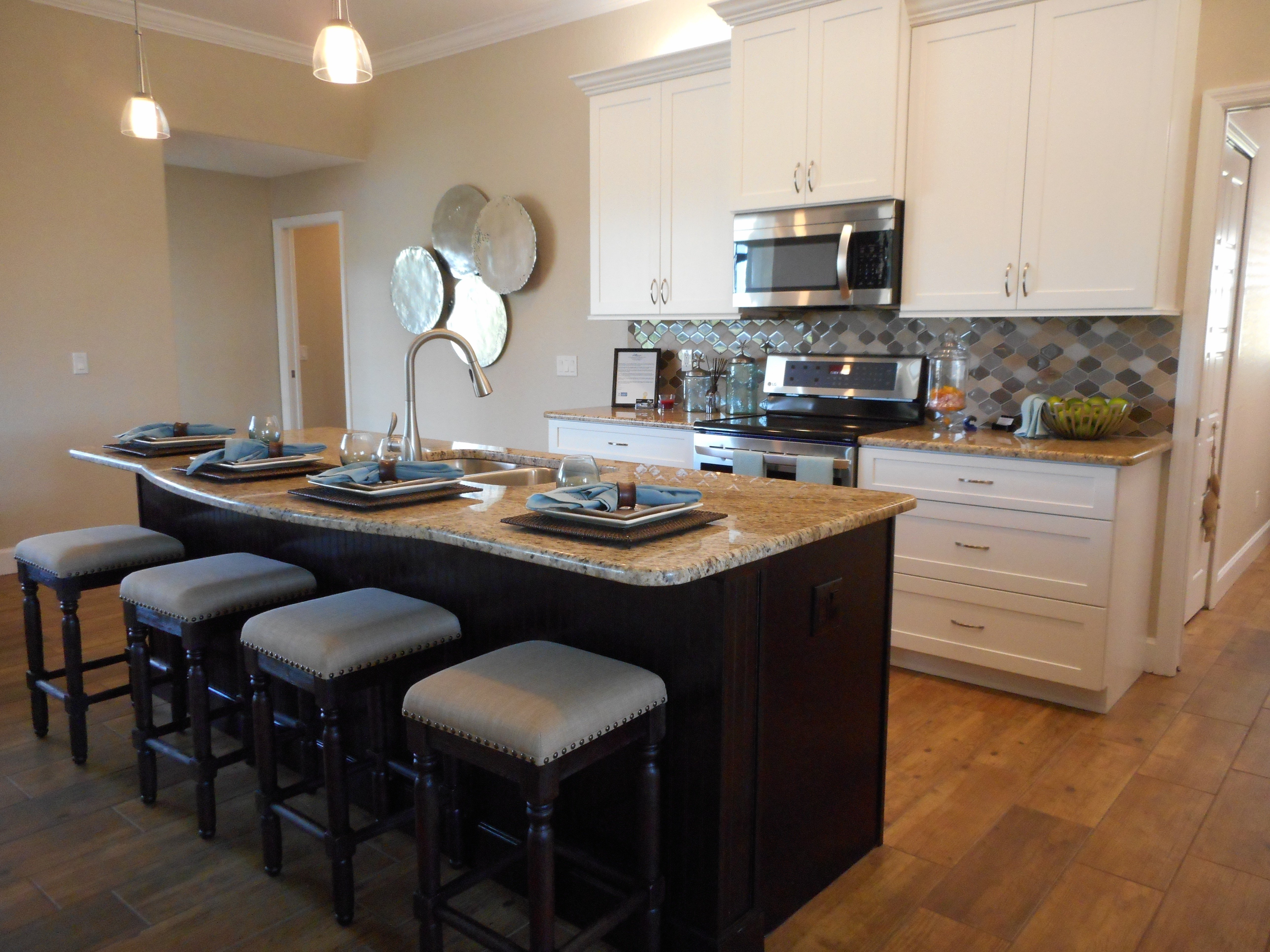 Staged photo of a kitchen with an island bar suited for four and wood floors.