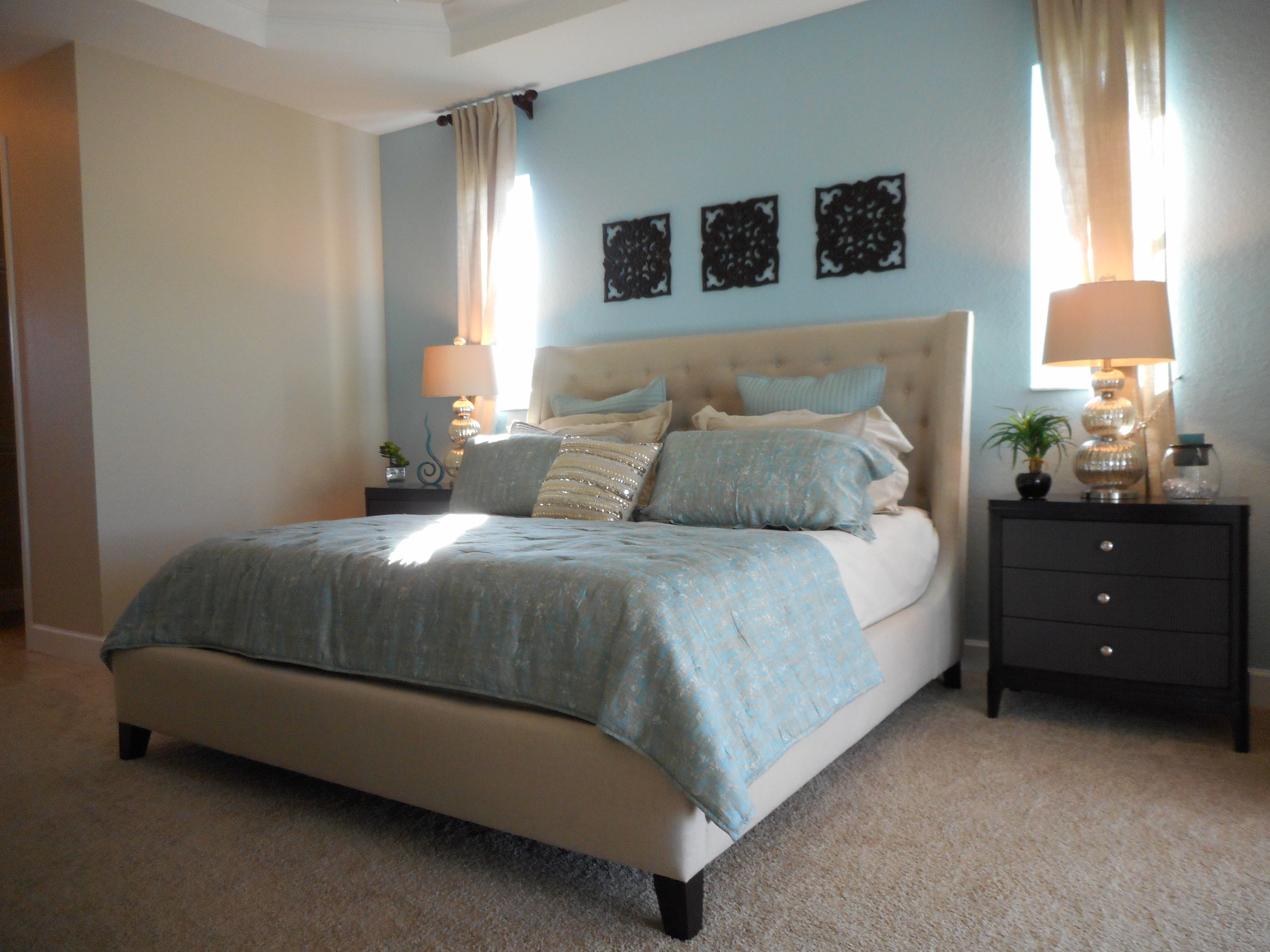 Bedroom with a queen sized bed and a night stand with a lamp.