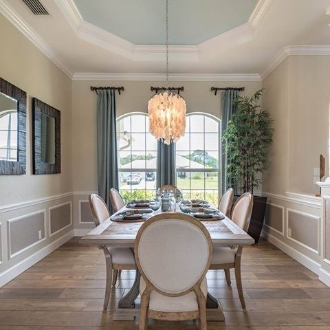 Dining room with wood floors, two large windows and a chandelier.