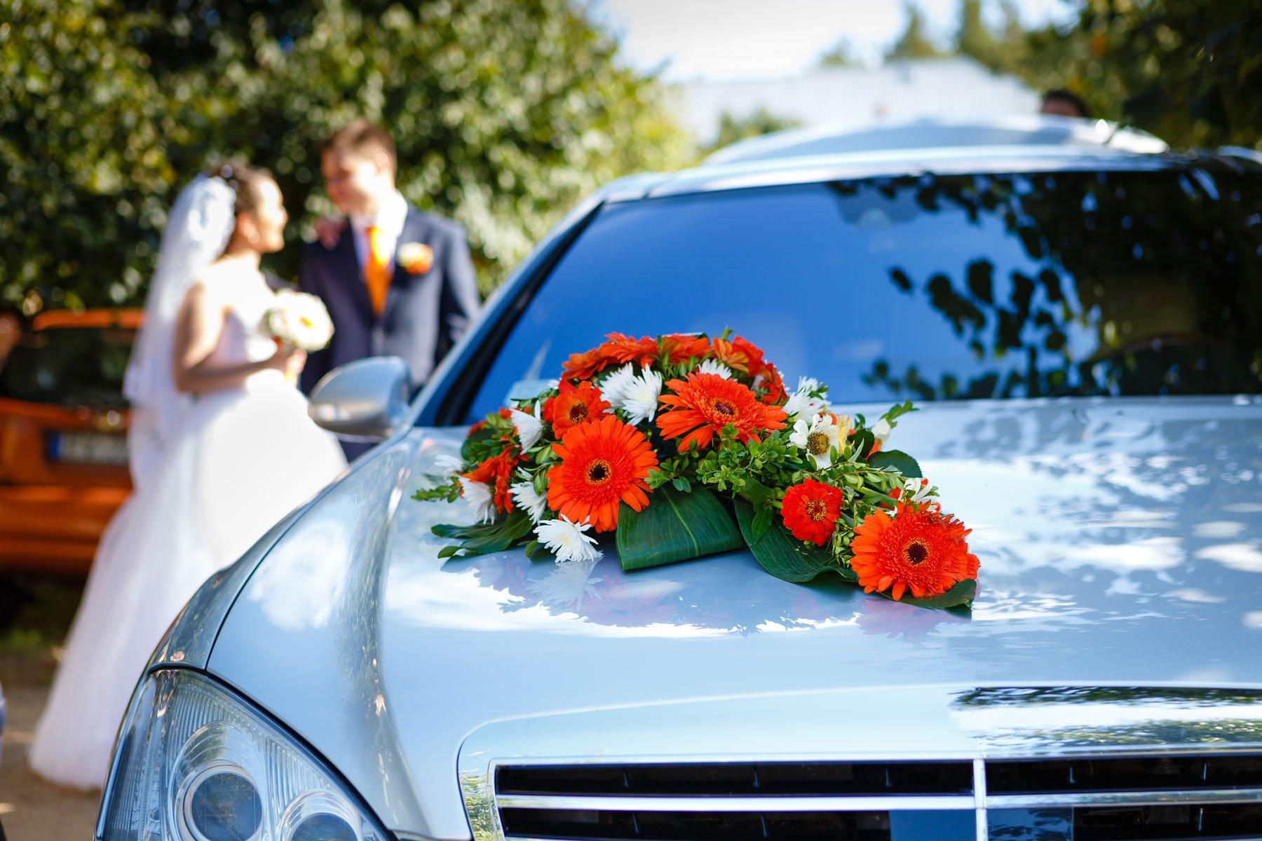 Una macchina con dei fiori sul cofano e due sposi sulla destra