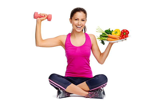girl in sports wear holding a weight and a plate of vegetables