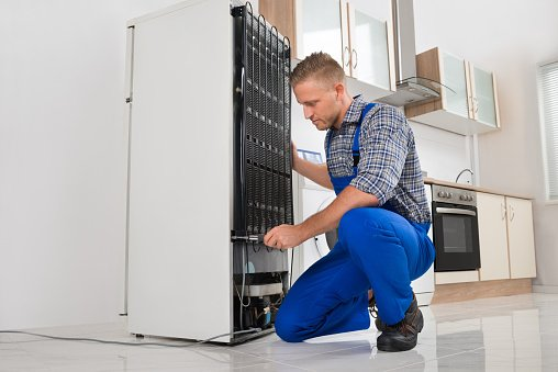 repairman working on refrigerator