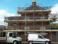 Our vans outside a house covered in scaffolding