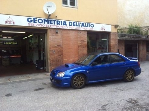 auto blu parcheggiata davanti all`autofficina GEOMETRIA DELL`AUTO