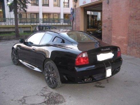 auto Maserati nera vicino a un garage