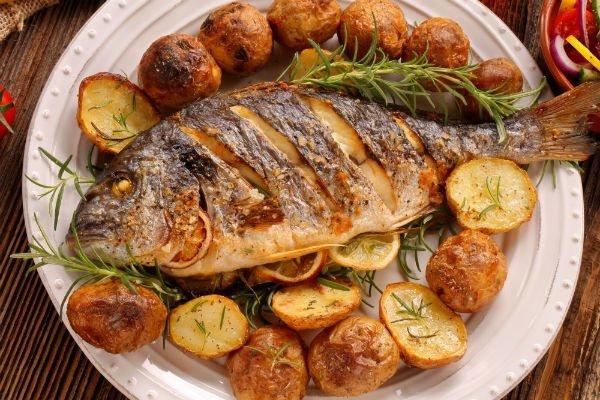 un piatto con un'orata alla griglia e patate
