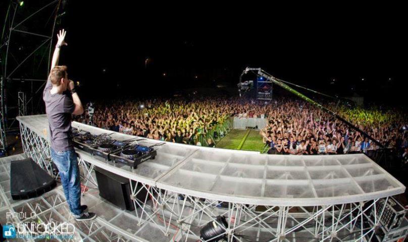 Cantante sul palco visto da dietro e folla tutta davanti