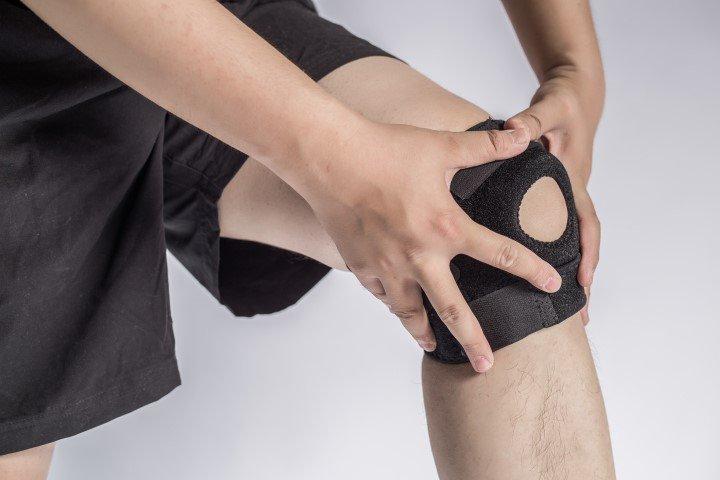 due mani appoggiate su un ginocchio con un tutore