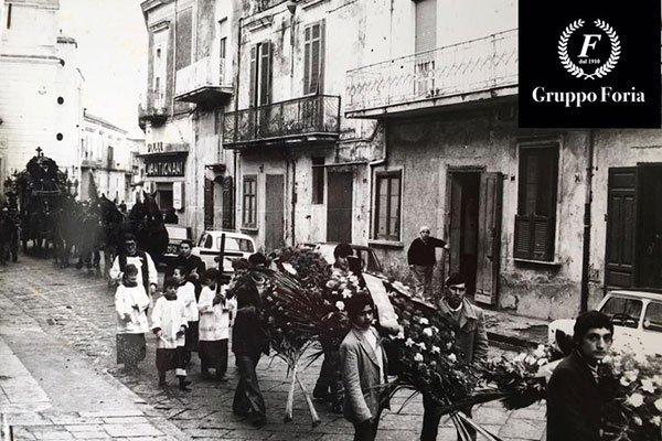 persone al funerale che trasportano le corone di fiori