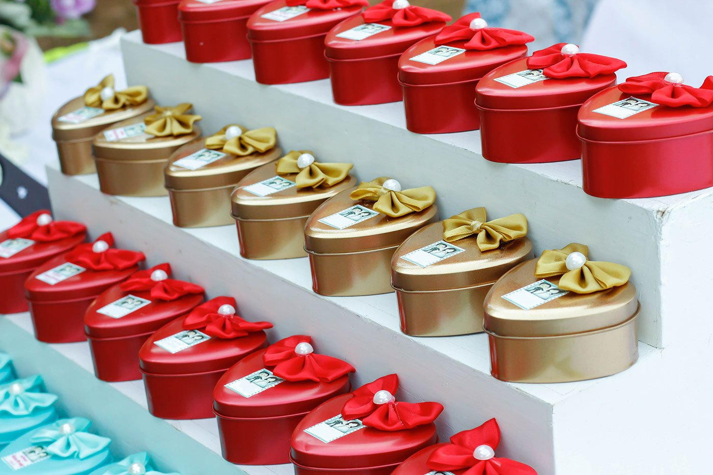 Scatoline a forma di cuore di color rosso,azzurro  e dorato con un fiocco sopra appoggiate sulle mensole