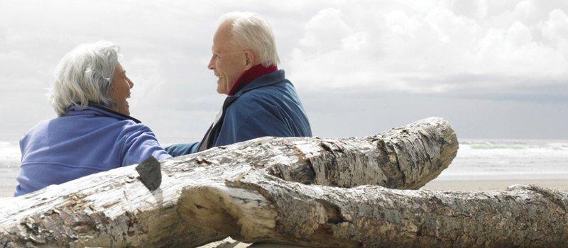 Elderly couple sitting next to drift wood
