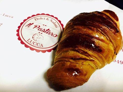 croissant con miele di fianco al logo della pasticceria