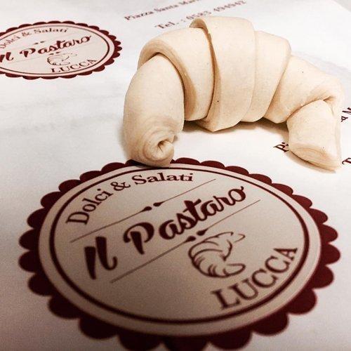 Croissant crudo di fianco al logo della pasticceria