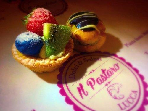 Inquadratura dall'alto di paste alla frutta di fianco al logo della pasticceria