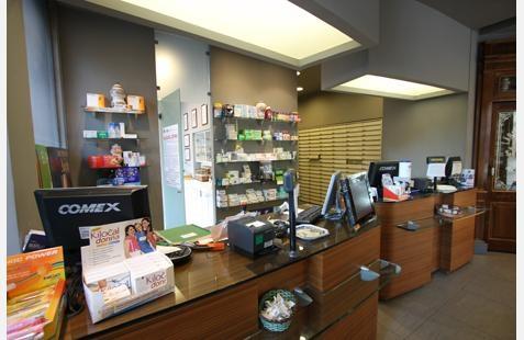 il bancone di una farmacia e vista delle mensole con i prodotti