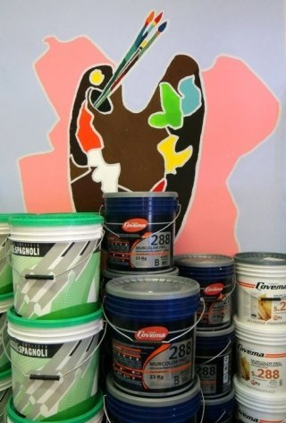 barattoli di vernice davanti a un muro dipinto