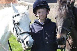 boy standing between 2 horses