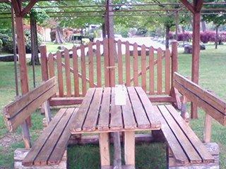un tavolo,delle panchine e un cancello in legno sotto a un gazebo
