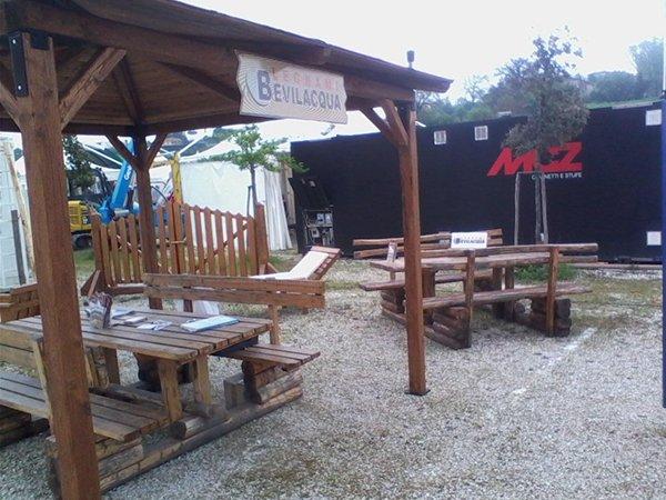 un gazebo in legno, tavoli, panchine e un cancello