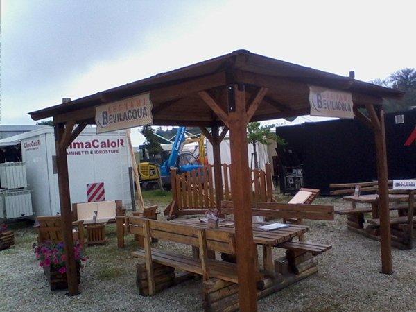 un gazebo in legno con scritto Bevilacqua e delle panchine,dei tavoli e altro materiale in legno