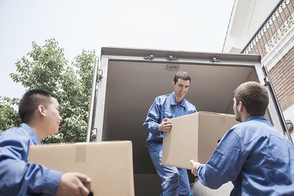 Uomini portando scatole del camion dei traslochi