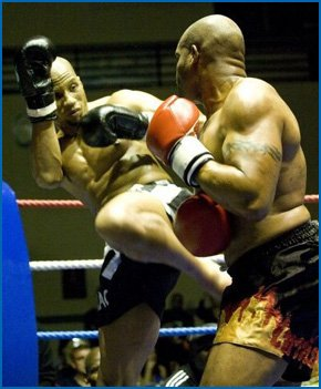Two men kickboxing in a ring.