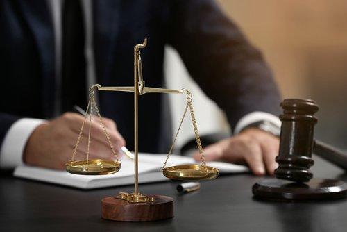 bilancia della giustizia e martello da giudice con uomo sullo sfondo