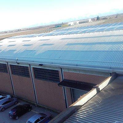 un tetto di una fabbrica e sotto dalle macchine parcheggiate