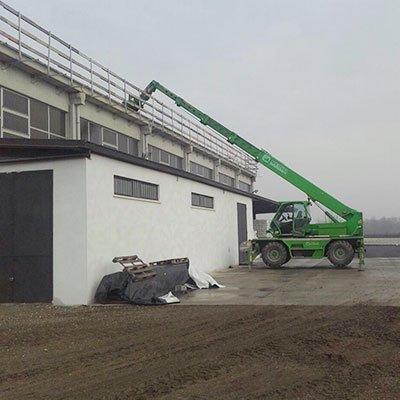 un mezzo da lavoro con un braccio meccanico verde vicino a uno stabile