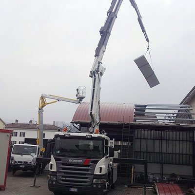 un camion con un braccio meccanico che solleva una lastra