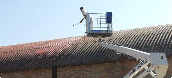 un uomo su una piattaforma elevatrice con un braccio meccanico che spruzza dell'acqua su un tetto
